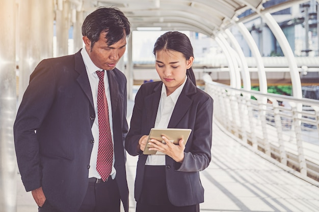 Business team working at city, looking a tablet Premium Photo