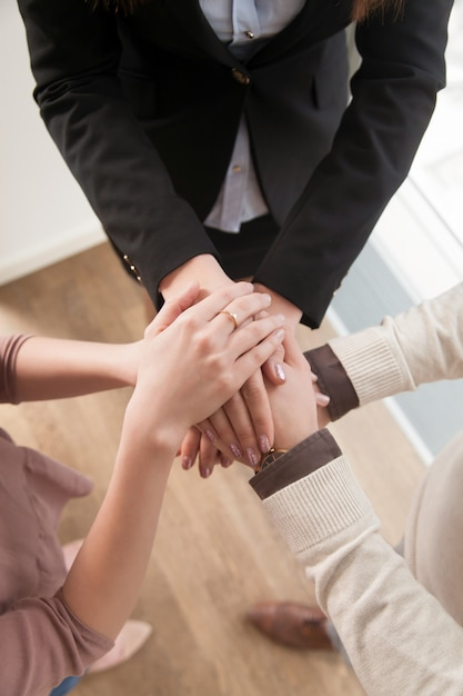 Business teamwork concept, top view of hands joined together, vertical Free Photo