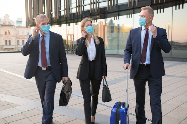 Business tourists in face masks travelling with briefcases or suitcase, walking outdoors, talking to each other. front view. business trip and epidemic concept Free Photo