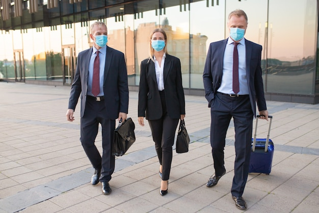 Business tourists in face masks visiting foreign partner office, wheeling suitcase, walking outdoors. front view. business trip and epidemic concept Free Photo
