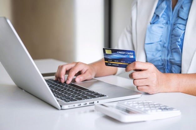 Business woman consumer holding credit card and typing on laptop for online shopping and payment make a purchase on the internet, online payment, networking and buy product technology Premium Photo