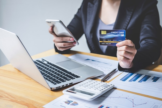 Business woman consumer holding smartphone, credit card and typing on laptop for online shopping and payment make a purchase on the internet, online payment, networking and buy product technology Premium Photo