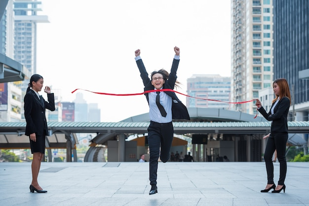 Business woman crosses the finish line to win on city background, business concept. Premium Photo