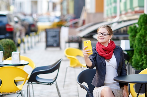 Business woman in glasses sitting at a table in a cafe and makes selfie Premium Photo