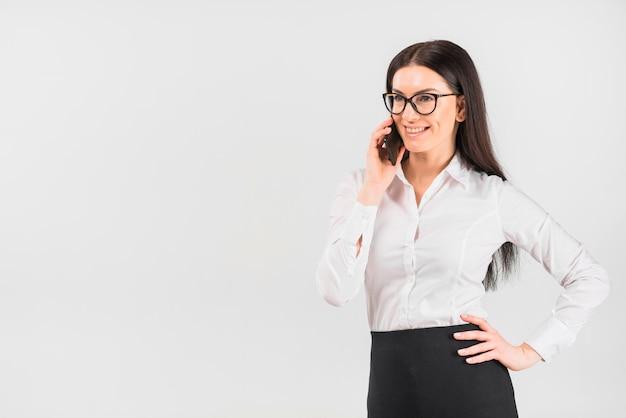 Donna di affari in vetri che parla dal telefono Foto Gratuite