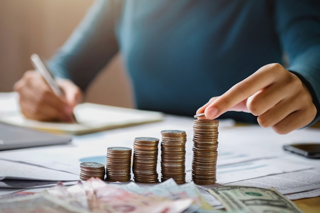 Business woman hand holding coins to stack on desk concept saving money finance and accounting Premium Photo