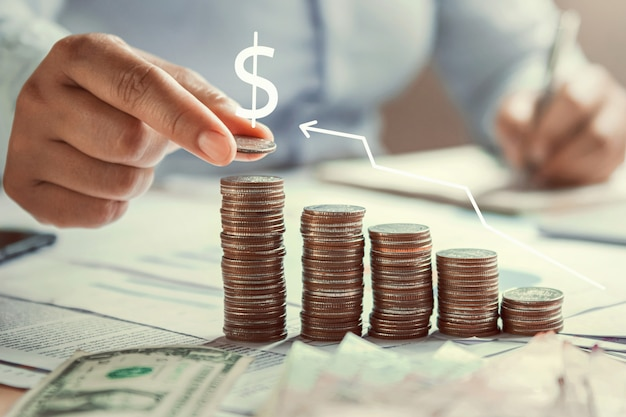 Business woman hand holding coins to stack on desk concept saving money finance Premium Photo