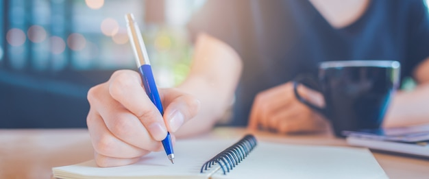 Business woman hand is writing on a notepad with a pen. Premium Photo
