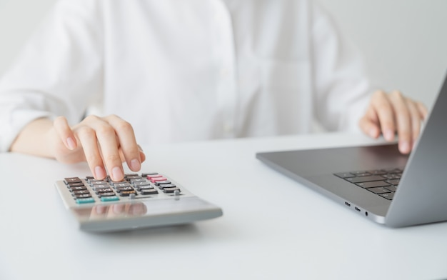 Business woman hand press calculator and calculate monthly expenses on table in office home. Premium Photo