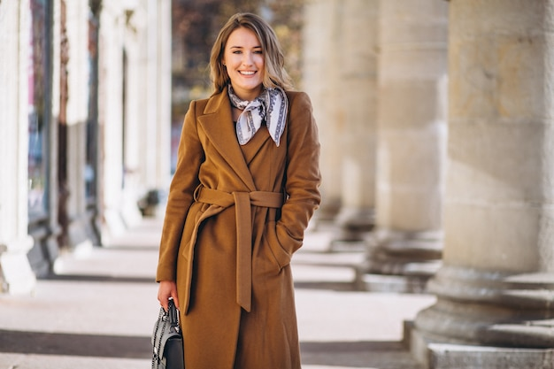 Business woman happy in coat in the street Free Photo