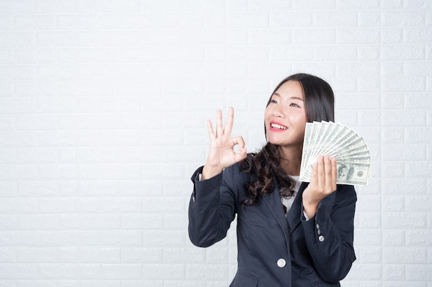 Business woman holding banknote, cash separately, white brick wall made gestures with sign language. Free Photo