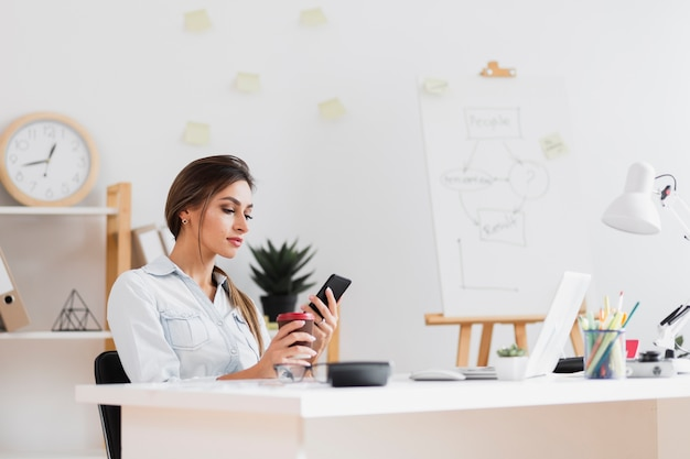 Business woman holding a cup of coffee and looking on phone Free Photo