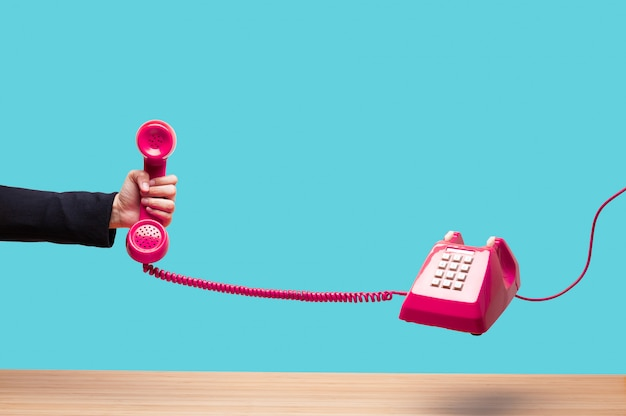 Business woman holding the red phone Premium Photo