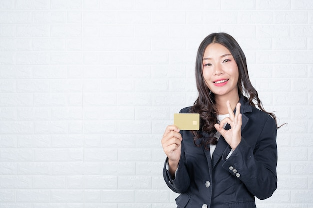 Business woman holding a separate cash card, white brick wall made gestures with sign language. Free Photo