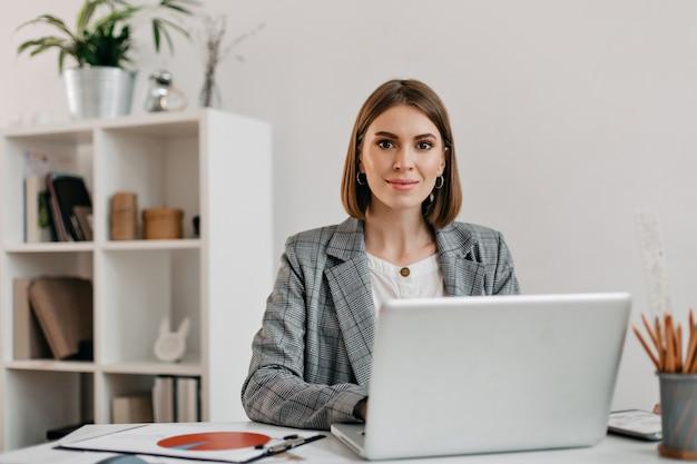 그녀의 사무실에서 책상에 앉아있는 동안 미소로 체크 무늬 재킷에 비즈니스 여자. 무료 사진