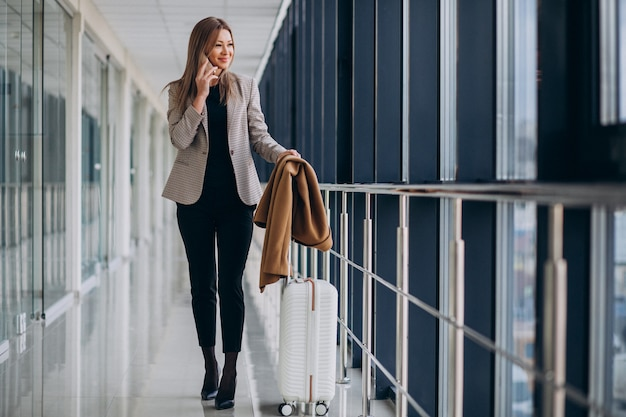 電話で話しているトラベルバッグとターミナルのビジネスウーマン 無料写真