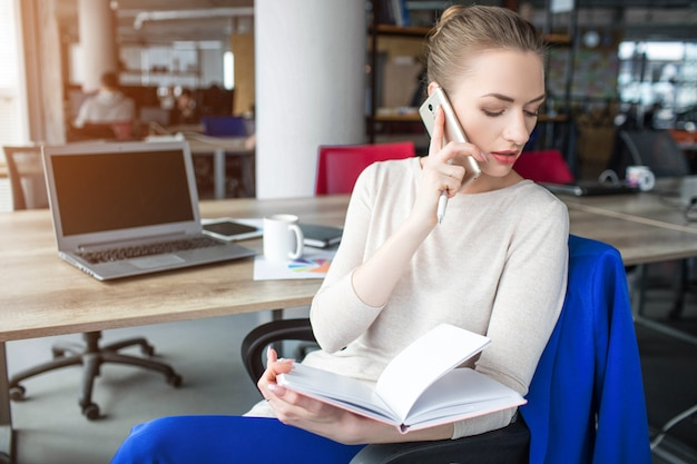 Business woman is sitting in chair and holding notebook. also she is talking on the phone. woman is looking down to the left. she is concentrated on that. Premium Photo