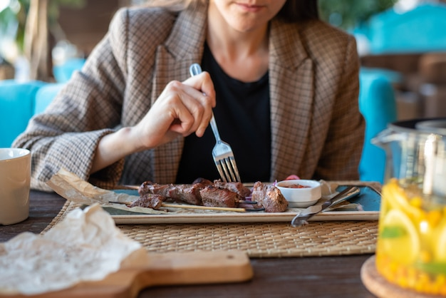 Business woman in jacket close-up in restaurant with cutlery eating grilled meat Premium Photo