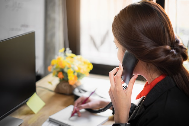 Business woman note schedule on book and talking with customer by telephone. Premium Photo