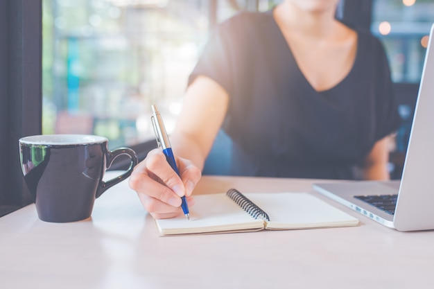 Business woman's hand is writing on a notebook with a pen. Premium Photo