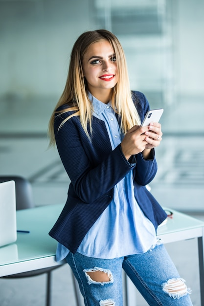 Business woman sending message with smartphone in office Free Photo