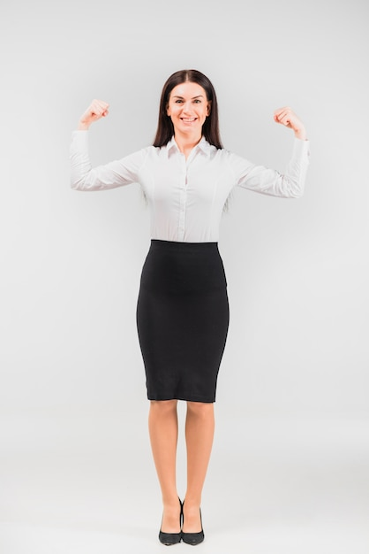 Business woman showing arm muscles Free Photo
