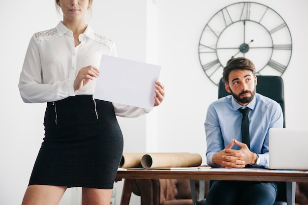 Business woman showing paper in office Free Photo