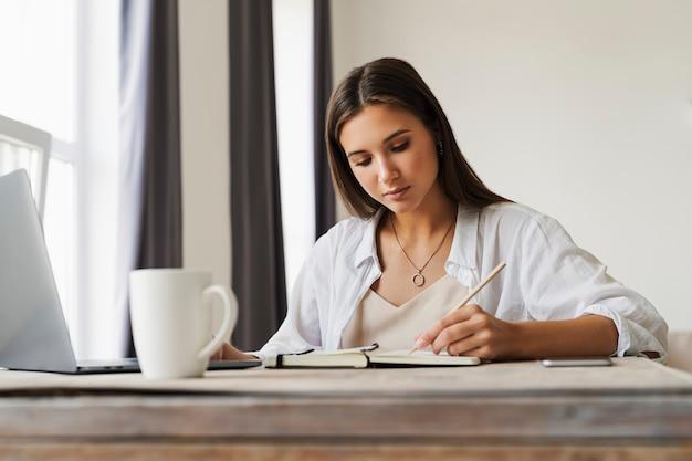 ビジネスウーマンはラップトップのテーブルに座って、スマートフォンはテーブルの上に横たわって、ノートに鉛筆でメモを作成します。 Premium写真
