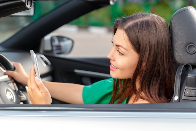 Business woman sitting in car and using her smartphone. Premium Photo