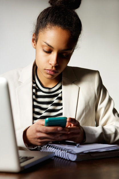 Business woman sitting at desk with mobile phone Premium Photo