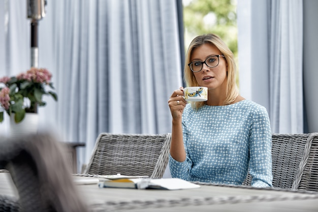 Business woman smiling with coffee at a table on the summer terrace. Premium Photo