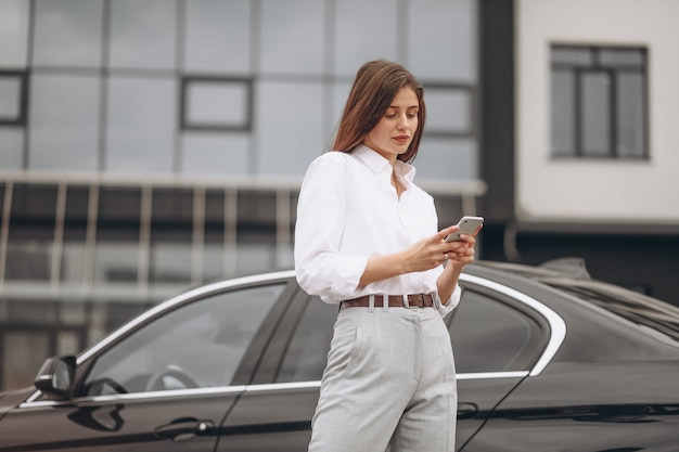 Business woman standing by the car and using phone Free Photo