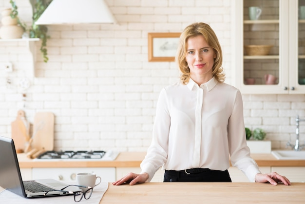 Business woman standing at table with laptop Free Photo