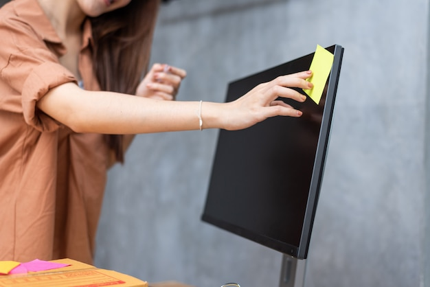Business woman sticking order list memo on computer screen for reminding to send parcels Premium Photo