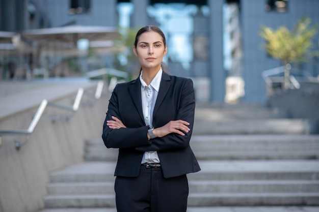 Business woman in a suit standing with arms folded Premium Photo