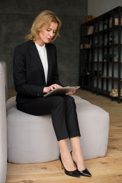 Business woman in suit using tablet Free Photo