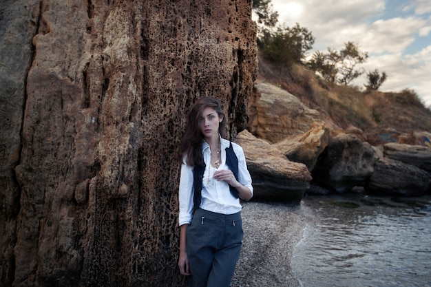 Business woman on suit vest and white shirt standing near big stone on the sea cost Premium Photo