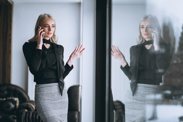 Business woman talking on the phone by the window Free Photo