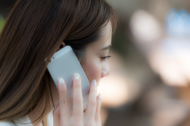 Business woman talking on smartphone on natural background, close up. Premium Photo