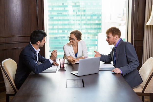 Business woman talking with two businessmen Free Photo