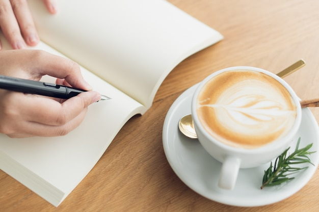 Business woman, traveler, article writer hold the pen to write the text in the empty book. Premium Photo