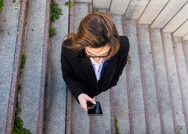 Деловая женщина с помощью смартфона на лестнице Бесплатные Фотографии