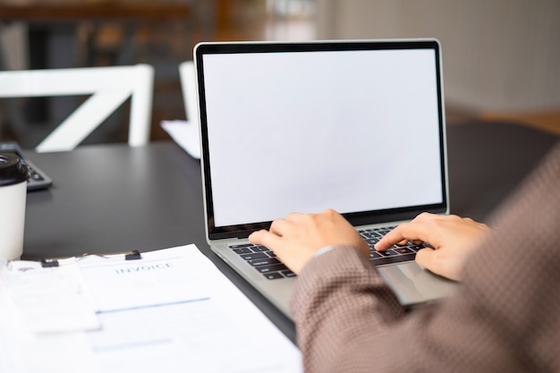 Business woman using and typing on mockup white screen laptop at her office. Premium Photo