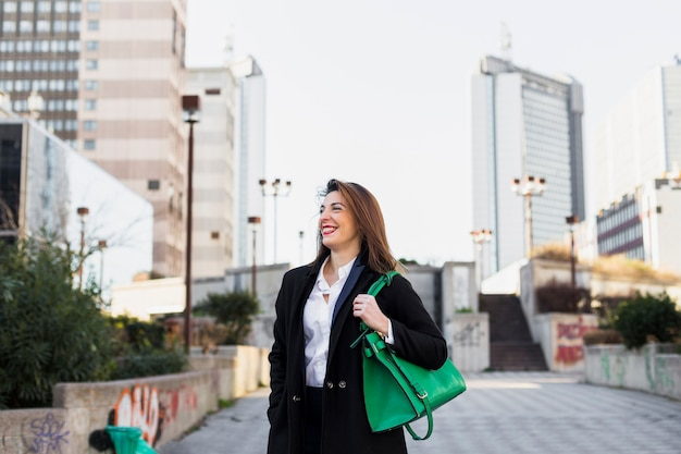Business woman walking in street with bag Free Photo