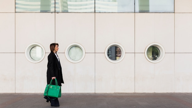 Business woman walking in street with green bag Free Photo