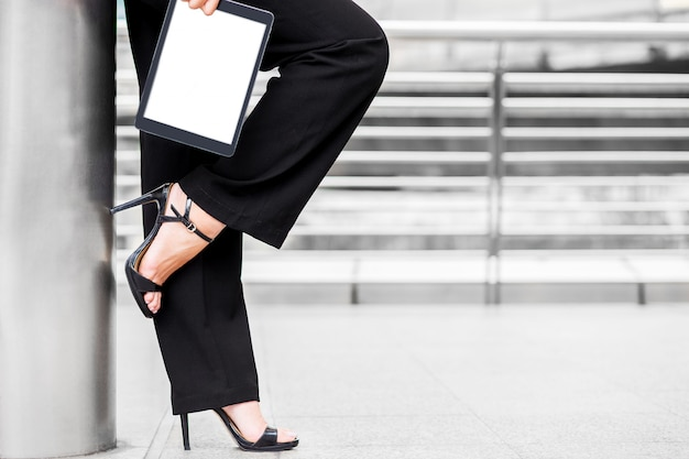 Business woman wear high heel and hold tablet Premium Photo