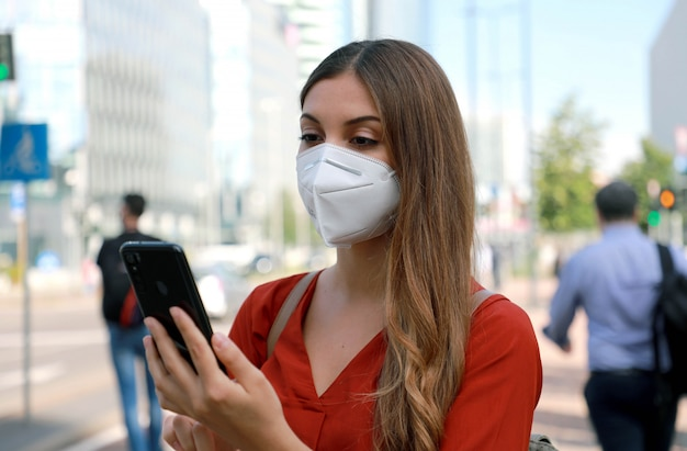Business woman wearing kn95 ffp2 face mask walking in modern city street holding a smartphone Premium Photo