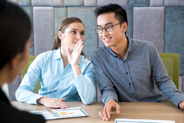 Business woman whispering secret to male colleague Free Photo