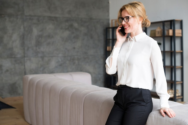 Business woman in white shirt talking on phone Free Photo