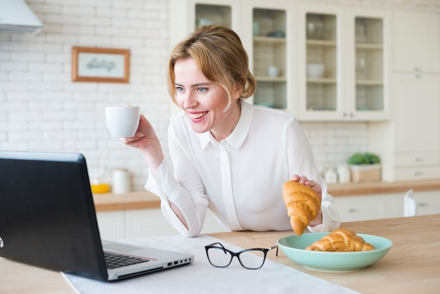 Business woman with croissant using laptop Free Photo